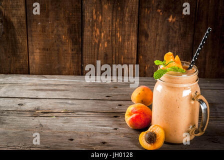 Smoothie bio faits maison à partir de yaourt et de l'abricot. En pot Mason, sur une vieille table en bois rustique, Banque D'Images