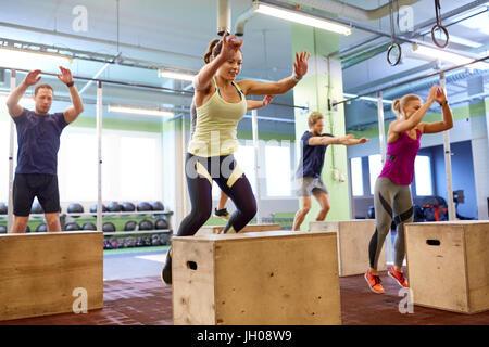 Groupe de personnes faisant des sauts de l'exercice dans la salle de sport Banque D'Images