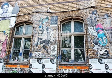 L'art du graffiti affiche sur un bâtiment en brique dans le quartier Kreuzberg de Berlin, Allemagne satellite commentaire Banque D'Images