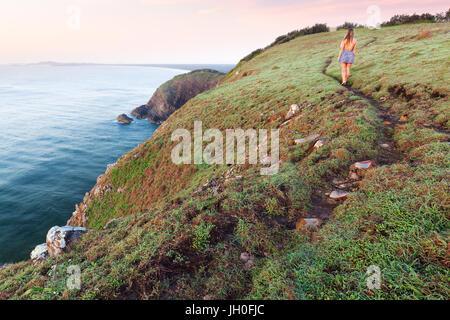 Une femme dans une robe marche sur un sentier herbeux à côté d'une falaise au-dessus de l'océan au lever du soleil Banque D'Images