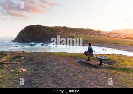 Une femme assise sur un banc en bois et regarde le golden sun light de disparaître de la magnifique côte autour Banque D'Images
