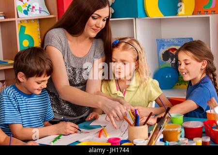 Petite fille aux étudiants la peinture au doigt en art school class. Banque D'Images