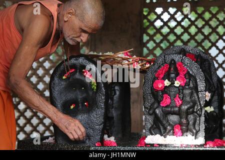 Temple Hindou dévot de placer des fleurs sur murthis Raman en reti. L'Inde. Banque D'Images