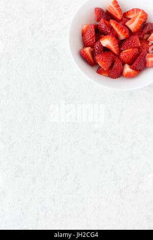Couper les fraises dans un bol en porcelaine blanc isolé sur fond de marbre blanc avec beaucoup d'espace de copie. Banque D'Images