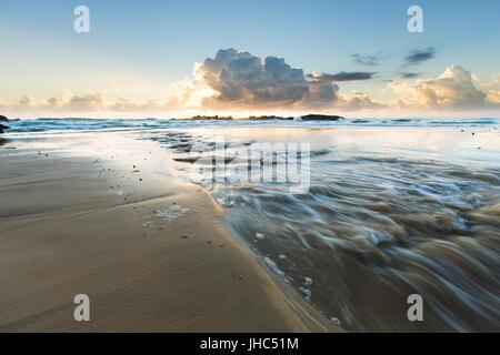 Un flux d'eau douce se jette dans la mer sur une belle plage vide en Australie comme les nuages sont éclairés par Banque D'Images