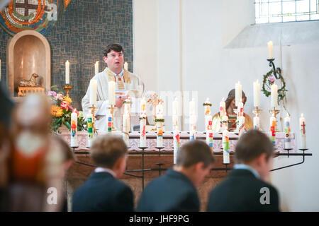 NANDLSTADT, ALLEMAGNE - le 7 mai 2017: un prêtre tenant la masse à la première communion avec les jeunes garçons Banque D'Images