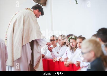 NANDLSTADT, ALLEMAGNE - le 7 mai 2017: le prêtre donnant aux jeunes garçons et filles, le pain sacramentel lors Banque D'Images