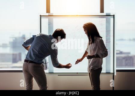 L'homme et de la femme entrepreneurs écrit des idées d'entreprise sur tableau blanc. Les investisseurs d'affaires Banque D'Images