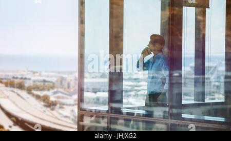 Portrait par fenêtre et talking on mobile phone. Homme debout à l'intérieur de bâtiment de bureaux et l'utilisation Banque D'Images