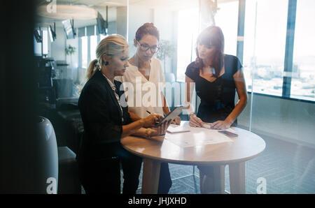 Dans un bureau de réflexion créative. Les gens d'affaires debout à la table et discuter de nouveaux projets. Banque D'Images