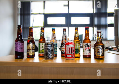 Une sélection de bières assis sur un bureau avec une lumière qui brille dans l'arrière-plan. Banque D'Images