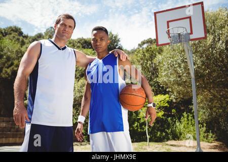 Portrait de joueur de basket-ball avec bras autour de tandis que l'article en cour Banque D'Images