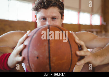 Close up portrait of male basketball player holding ball assis en cour Banque D'Images