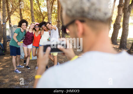 Vue arrière de l'homme photographie amis tout en se tenant à camping Banque D'Images