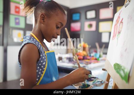 Vue de côté de l'accent girl painting on canvas in classroom Banque D'Images