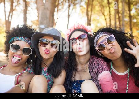 Portrait of happy female friends making faces while sitting ensemble au camping Banque D'Images