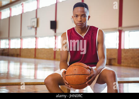 Portrait of male adolescent avec le basket-ball assis sur un banc en cour Banque D'Images