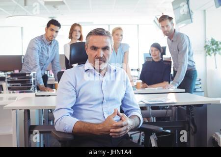 Portrait of serious businessman sitting on chair avec en arrière-plan de l'équipe at office Banque D'Images
