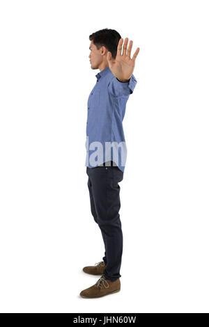 Vue de côté montrant l'homme tout en geste d'arrêt standing against white background Banque D'Images