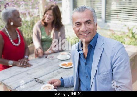 Portrait of smiling senior homme de boire du café avec des amis à table patio Banque D'Images
