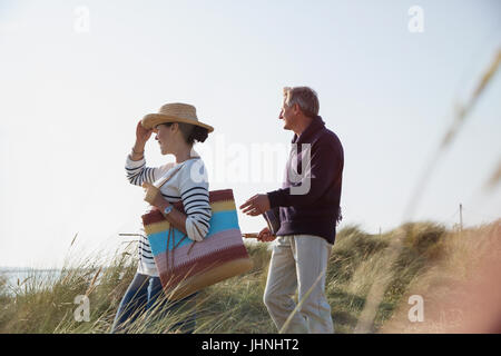 Mature couple walking on sunny beach chemin d'herbe Banque D'Images