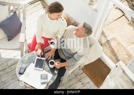 Vue de dessus mature couple drinking coffee and using digital tablet sur véranda Banque D'Images