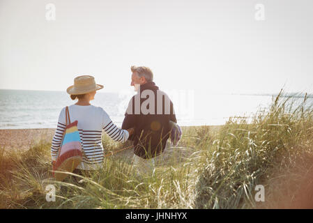 Mature couple walking arm in arm sur sunny beach Banque D'Images