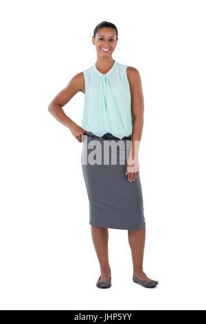 Smiling businesswoman standing avec sa main sur les hanches contre fond blanc Banque D'Images