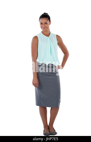 Smiling businesswoman standing with her hand on hip against white background Banque D'Images