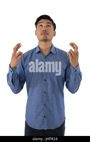 Businessman with crossed fingers à tout standing against white background Banque D'Images