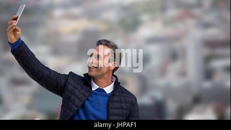 Digital composite de l'homme en manteau en tenant contre selfies ville floue Banque D'Images
