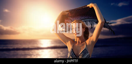 ... Smiling woman holding foulard en l air contre scenic view of sea  against sky Banque 288e5aa5a96