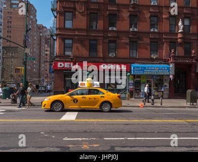 New York, NY USA -- 12 juillet 2017 -- un taxi est arrêté sur la 14e rue en attendant que le feu passe alors que deux piétons commencer à traverser la rue Banque D'Images