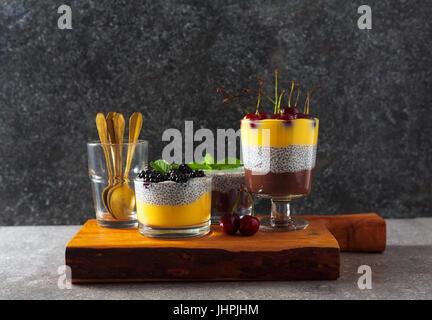 Desserts en couches de chocolat et vanille pudding et aussi de graines de chia avec des cerises mûres sur le dessus Banque D'Images