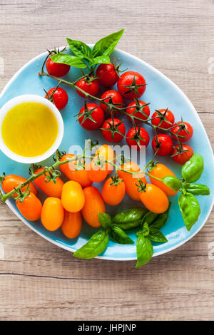 Variété de tomates cerise et les feuilles de basilic sur une plaque bleue sur une table en bois. Ingrédients pour Banque D'Images