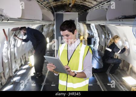 Technicien d'entretien d'aéronefs femelle using digital tablet in d'un avion à l'installation de maintenance des Banque D'Images