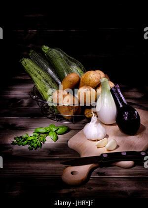 Les pommes de terre, courgettes, oignons, ail, basilic et persil photographié sur une antique table en bois avec Banque D'Images