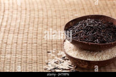 Black le riz sauvage et le riz basmati dans des bols sur un fond de paille Banque D'Images