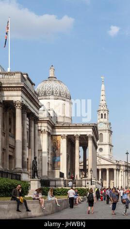 Les touristes et les habitants debout et assis à l'extérieur de la galerie sur Trafalgar Square, Londres, St Martin Banque D'Images