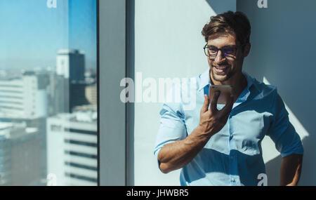 Businessman talking on phone orateur debout à côté d'un immeuble de bureaux de grande hauteur de la fenêtre. Smiling Banque D'Images