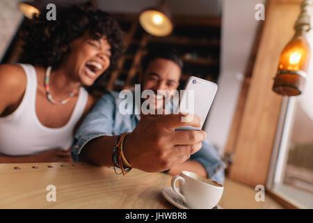 Jeune couple à prendre un café à l'aide de selfies téléphone intelligent. Jeune homme et femme en riant tout en Banque D'Images