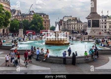 Les touristes et les habitants, les familles et les amis autour d'une fontaine à Trafalgar Square, au centre de Banque D'Images