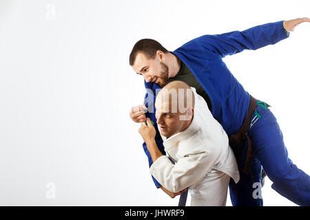 Deux jeunes hommes dans un kimono bleu et blanc lutte judo jiu jitsu , sur un cas isolé sur fond blanc
