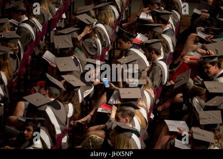Jeunes diplômés portant des blouses et loué mortarboards regarder les médias sociaux dans le hall central de leur Banque D'Images