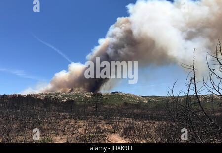 Corse, France. 17 juillet, 2017. Des nuages de fumée d'un incendie de forêt brûlée de buissons, à quelques kilomètres Banque D'Images