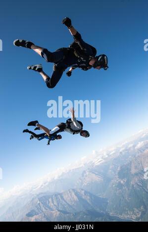 Quatre parachutistes de l'alignement sur un système d'aller au-dessus de Locarno, Suisse, avec les Alpes en arrière Banque D'Images