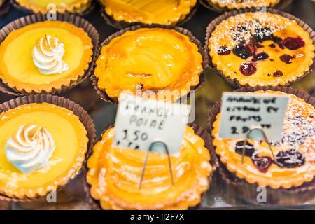 Petites tartelettes au citron meringuée chantilly avec les blancs sur l'écran dans une boulangerie avec des enseignes Banque D'Images
