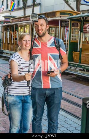 Un jeune couple britannique, en vacances, prendre un en face de l'selfies Powell & Hyde cable car à San Francisco. Banque D'Images