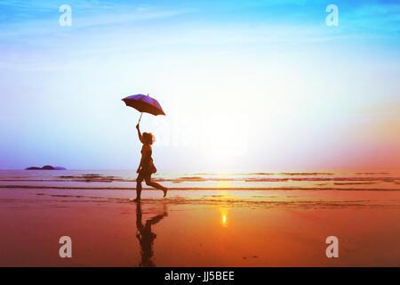 Silhouette de jeune fille insouciante heureux avec parapluie de sauter sur la plage au coucher du soleil, la liberté Banque D'Images
