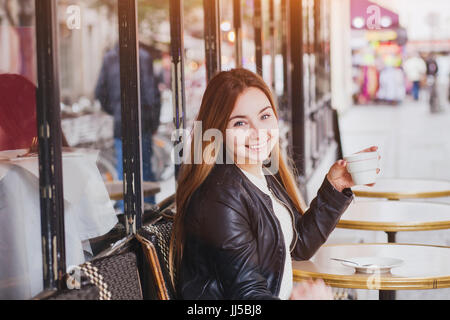 Happy smiling woman drinking coffee in street cafe and looking at camera, bonne humeur